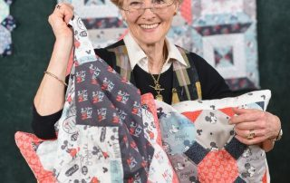 Jennie Rayment holding up quilt